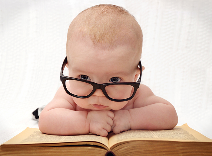 baby with glasses resting on a book